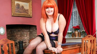 Curvy red cougar stripping and playing alone